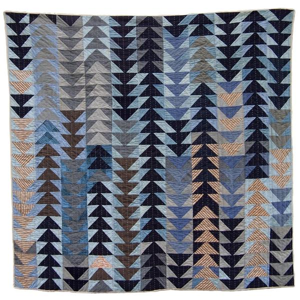 geometric quilt featuring a triangle pattern in blue tones and neutral colors