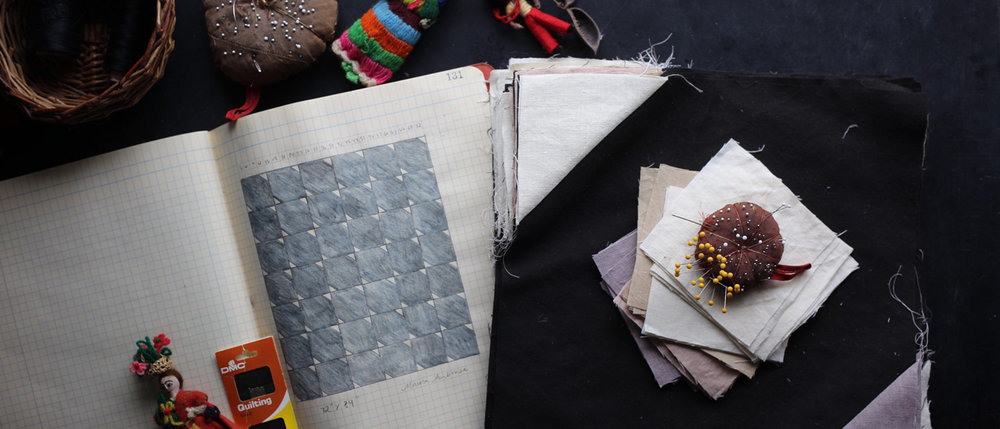 stacks of quilting and sewing materials on a desk
