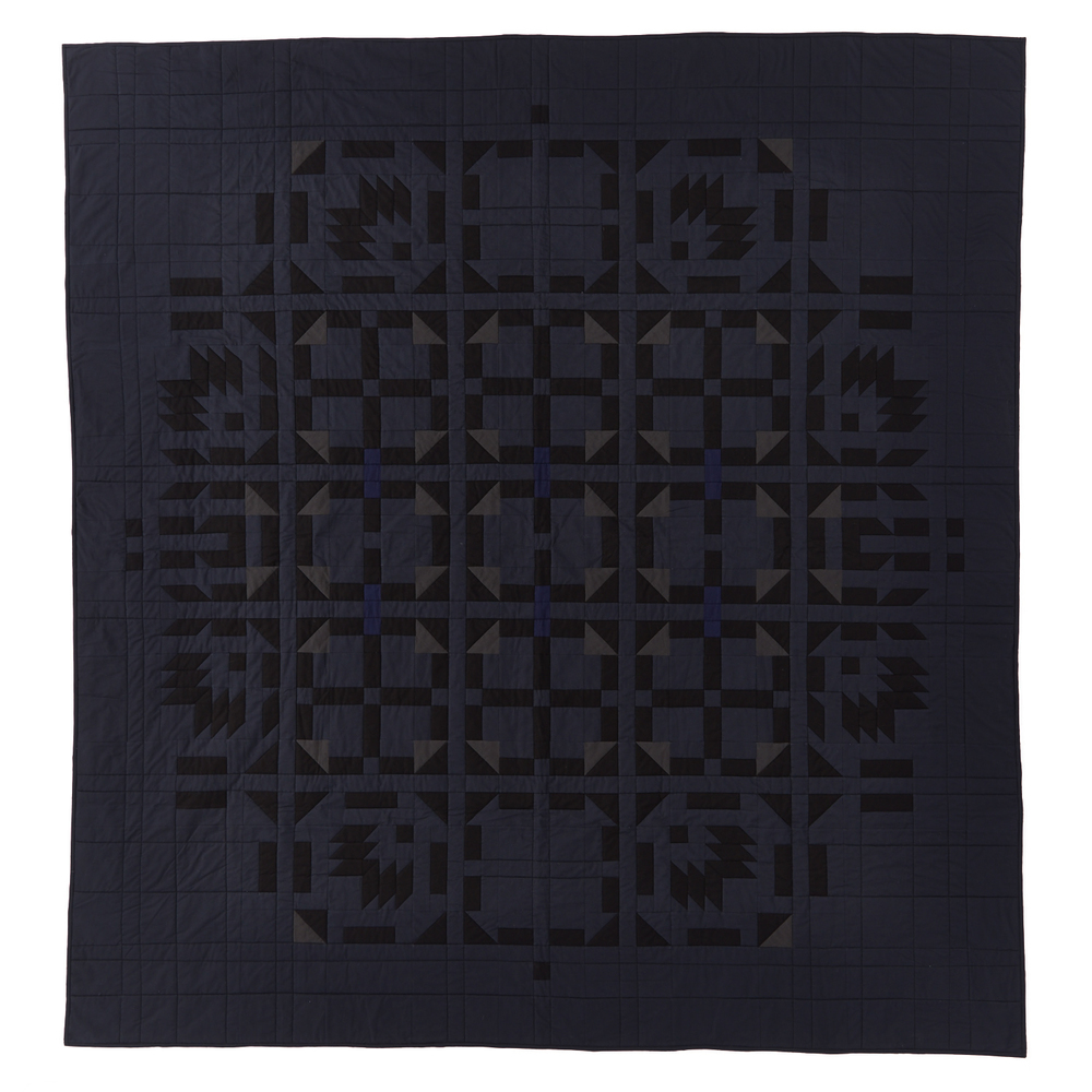 dark grey/blue geometric quilt featuring repeating patterns with triangles and squares
