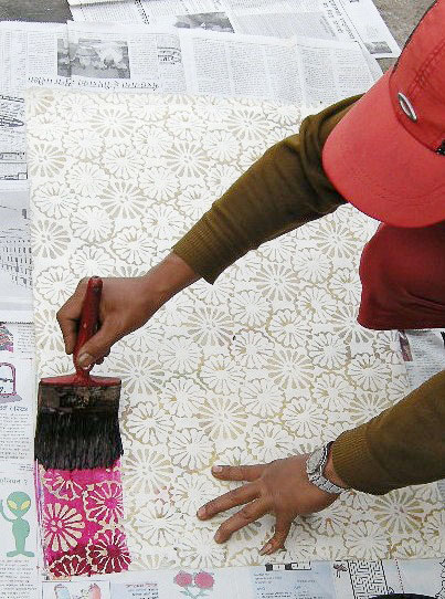 batik dyeing process completed by a man with a red hat and brown sweater painting magenta over white wax flower prints