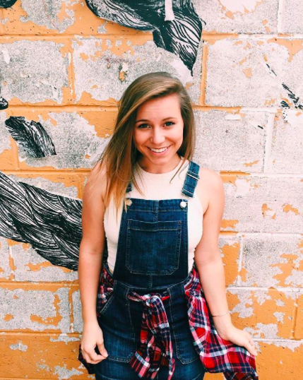 girl with blonde hair and overalls with flannel tied around waist