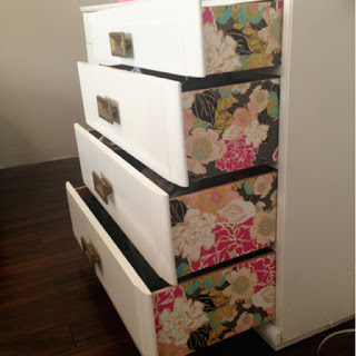 white dresser drawers pulled out reveling floral wallpaper